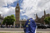 Un hombre con la bandera de la UE, cabizbajo ante el Big Ben.