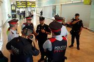 Agentes de los Mossos y la Policía Nacional, tras el anuncio de protestas con motivo de la sentencia del 'procés', en el aeropuerto de El Prat.