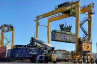 Grúas cargando contenedores en un tren en el puerto de Valencia.