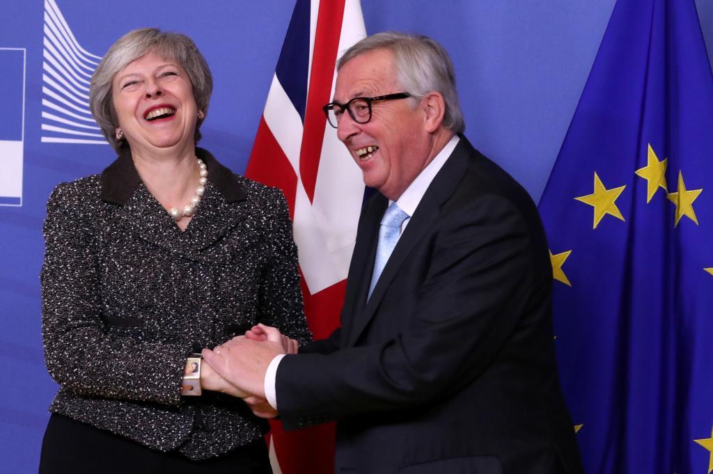 Theresa May y Jean-Claude Juncker estrechan la mano en Bruselas.