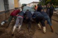 Un grupo de vecinos ayuda a retirar un vehículo arrastrado por el agua y el barro durante las inundaciones de octubre de 2018 en Campillos.