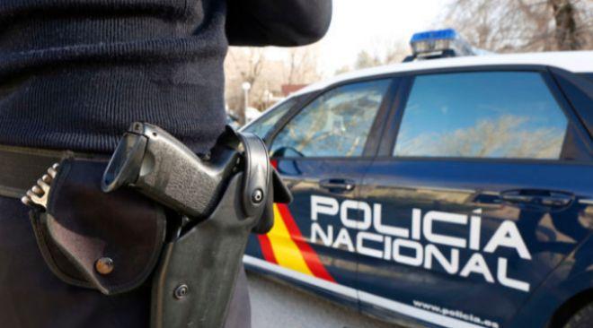 Un agente del cuerpo de Policía armado frente a su vehículo