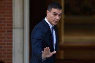 Pedro Sánchez hace un gesto a los reporteros gráficos antes de entrar en Moncloa para mantener una reunión con Pablo Casado.
