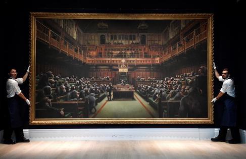 Dos operarios de Sotheby's exhiben 'Parliament Devolved', obra de Banksy.