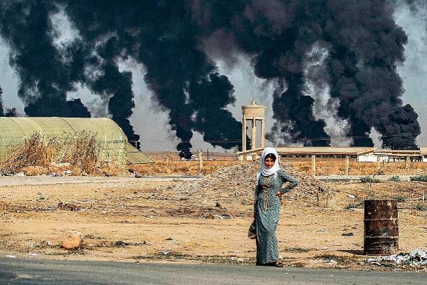 Una mujer en Tal Tamr, mientras al fondo se observan columnas de humo fruto de la operación turca.