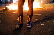 Un manifestante independentista con botas decoradas con la estelada catalana, en los disturbios, este martes, en Barcelona.