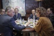La ministra en funciones, María Jesús Montero, conversa con Salvador Navarro (CEV), ante la mirada de Arturo León (CCOO), el presidente Puig, Ismael Sáez (UGT) y el conseller Soler.