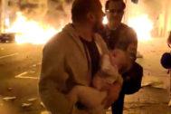 Un padre huye de su casa con su bebé en brazos asediado por las llamas de las protestas en Barcelona