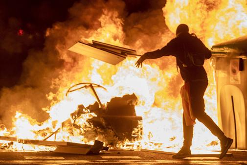Un manifestante lanza una tabla de madera a una barricada incendiada,...