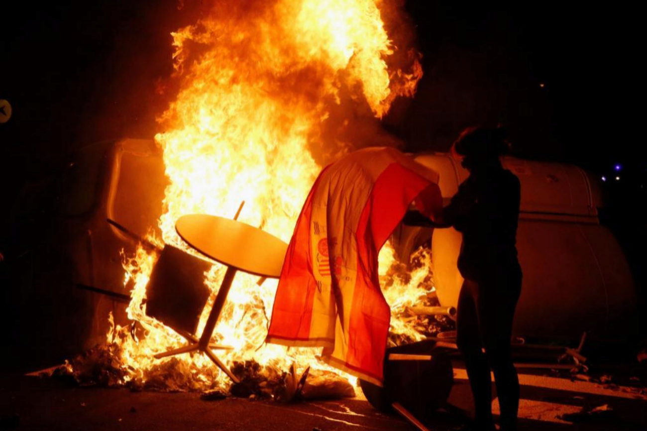 Un independentista quema una bandera española en una de las hogueras prendidas en Barcelona.