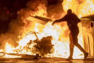 Un manifestante lanza una tabla de madera a una barricada incendiada, en Barcelona.