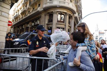 Un hombre y su hija entregan un ramo de flores a un policía en la Jefatura Superior de Via Laietana, en el centro de Barcelona.