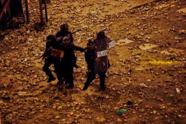 Un grupo de policías antidisturbios intenta protegerse del ataque sufrido en la noche de este viernes, en Barcelona.
