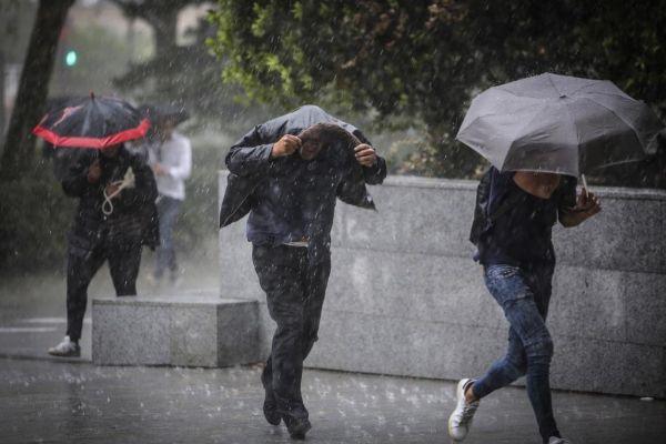 Varias personas se cobijan de la lluvia en una calle de Valencia.