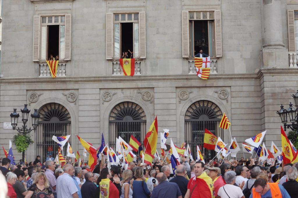 Banderas catalana, española y de la ciudad de Barcelona cuelgan en unas ventanas del Ayuntamiento.