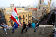 A demonstrator carries the national flag as he stands on the balcony of a building during an anti-government protest in downtown Beirut