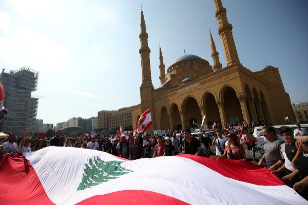Demonstartors holds a Lebanese flag during an anti-government protest...