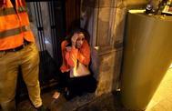 Una mujer se refugia en el portal de un edificio de los disturbios sucedidos en Barcelona.