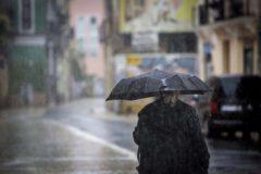 Una mujer se protege de la lluvia bajo un paraguas.