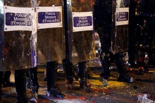 Agentes de los Mossos d'Esquadra se cubren con escudos ante las...