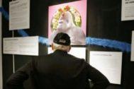Un espectador observa el montaje hecho con un gorila adornado con flores.