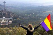 Una mujer ondeando la bandera republicana, ayer, en un monte desde donde se divisa el Valle de los Caídos.