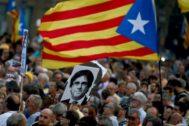 arios manifestantes portan una bandera 'estelada' junto a una fotografía del expresidente de la Generalitat de Cataluña, Carles Puigdemont.