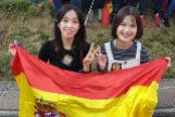 Dos jóvenes chinas enseñan una bandera española.