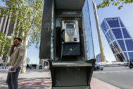 Un joven habla por teléfono al lado de una cabina telefónica pública en Madrid.