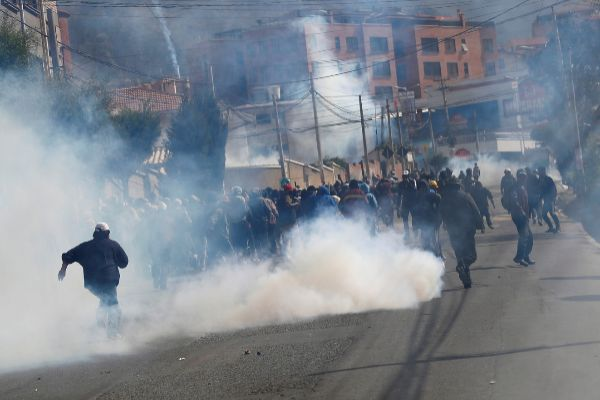 People run from tear gas during a protest in La Paz