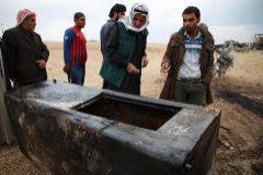 Ciudadanos sirios observan un contenedor quemado en la zona donde habría sido encontrado el cuerpo de Abu Hasan al Mujahir.