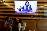 Dos jóvenes iraquíes miran una televisión en la que informan de la muerte de Abu Bakr al Bagdadi.