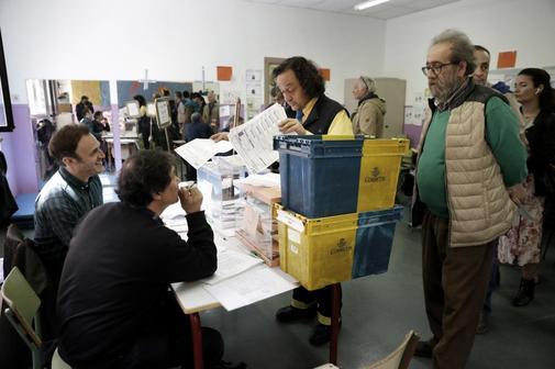 Un cartero entrega en una mesa electoral votos enviados por correo en...