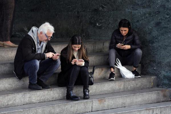 Tres ciudadanos consultan sus móviles en la calle.