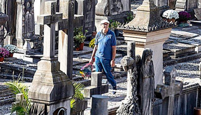 Un hombre entre tumbas y con un ramo de flores en el cementerio de Palma.