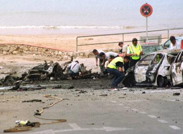 Miembros de la Policía inspeccionan los restos del coche bomba que explotó en Salou (Tarragona), en 2001.