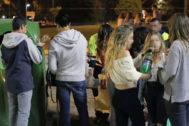 Grupo de adolescentes preparando combinados de bebidas en un 'botellón' en  la calle.