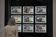 Una mujer observa carteles de alquiler en el escaparate de una agencia.