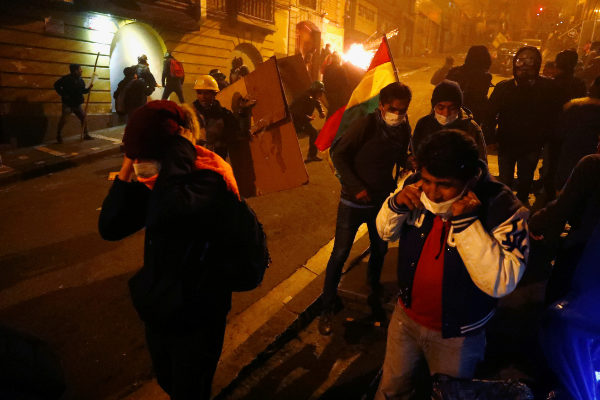 Protesters clash with riot police while demonstrating against Bolivian...