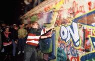 Un joven trata de derrumbar el Muro de Berlín con un hacha.