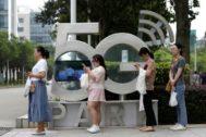 Ciudadanos chinos consultando sus terminales móviles ante un monumento 5G
