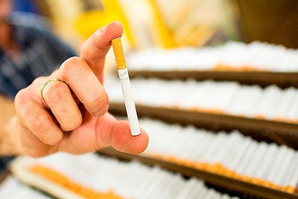 Una persona sostiene un cigarrillo de Imperial Brands.