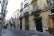 Dos viandantes pasan junto a la sede de la Agrupación Centro del PSOE de Málaga, en la calle Ollerías.