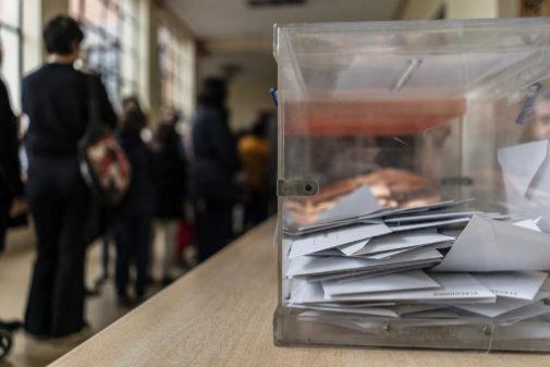 Varias personas hacen cola ante su mesa en un colegio electoral.