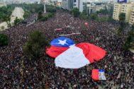 Manifestación con una bandera gigante de Chile, en Santiago de Chile.