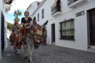 Dos turistas pasean por Mijas a lomos de un burro.