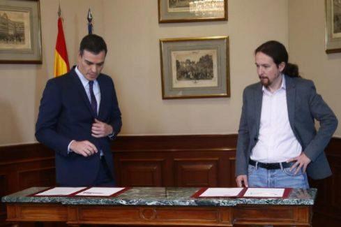 El candidato de Unidas Podemos, Pablo Iglesias (dcha.), observa como Pedro Sánchez se dispone a firmar el acuerdo, este martes, en Madrid.