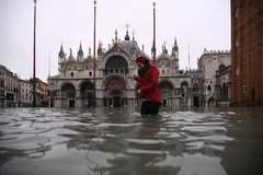 Una turista cruza la plaza de San Marcos, inundada.