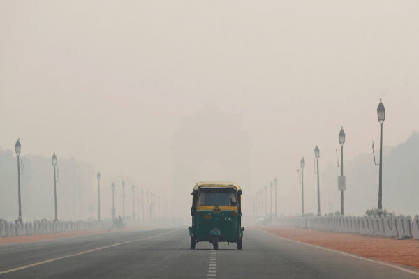 An auto-rickshaw moves past the India Gate on a smoggy morning in New...