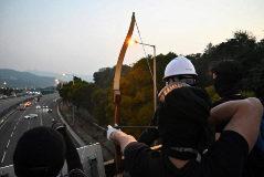 Un manifestante lanza una flecha a la carretera en Hong Kong.